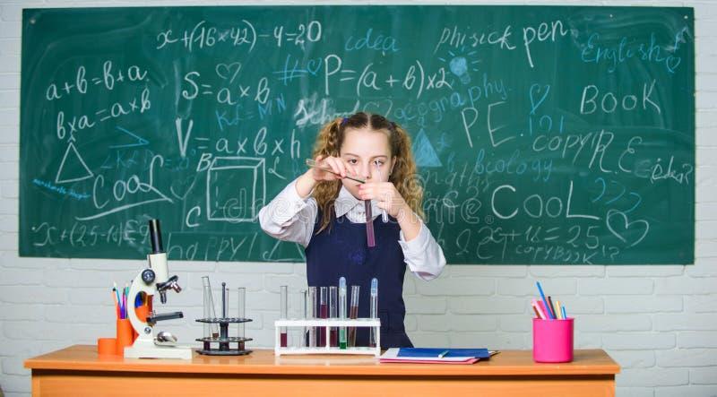Experiência esperta da escola da conduta do estudante da menina Líquidos químicos do estudo do aluno da escola Lição da química d foto de stock royalty free