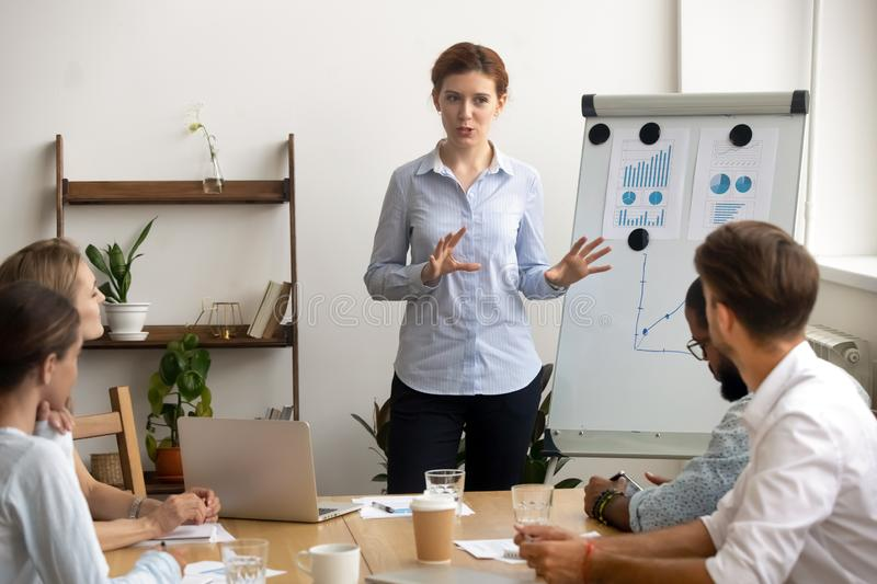 Experienced ambitious businesswoman gives presentation at team meeting near flipchart royalty free stock photo