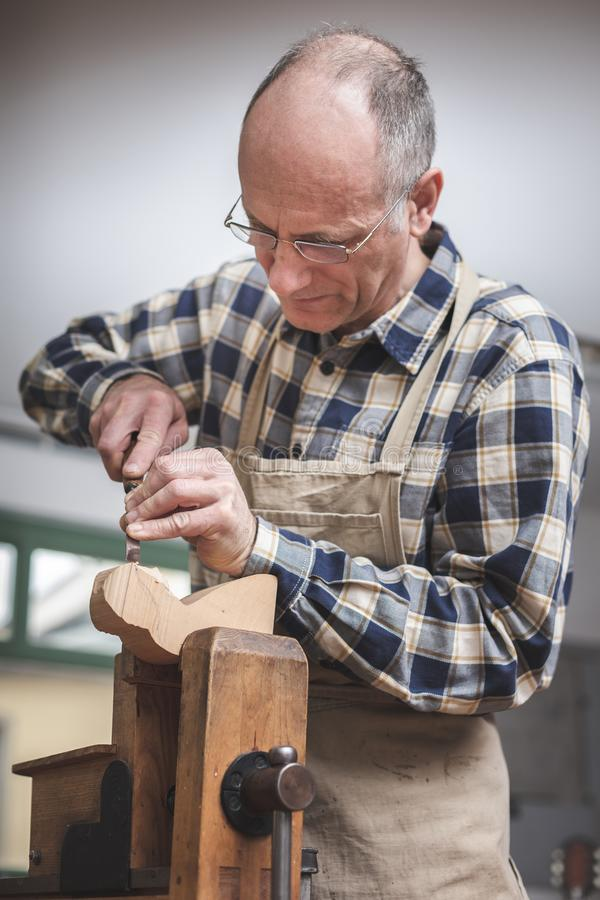 Experienced artisan focused on carving a piece of wood. Mature artisan carving a wooden figure at a rustic workbench. Upper body behind a bench vise royalty free stock photos