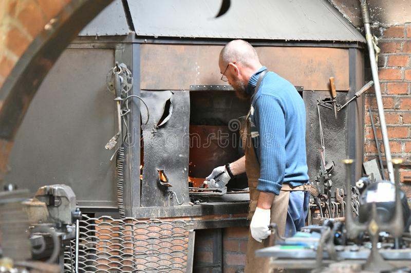 An experienced blacksmith works with open fire. A blacksmith extinguishes a flame in a forge with a spark firework, forges hot royalty free stock photo