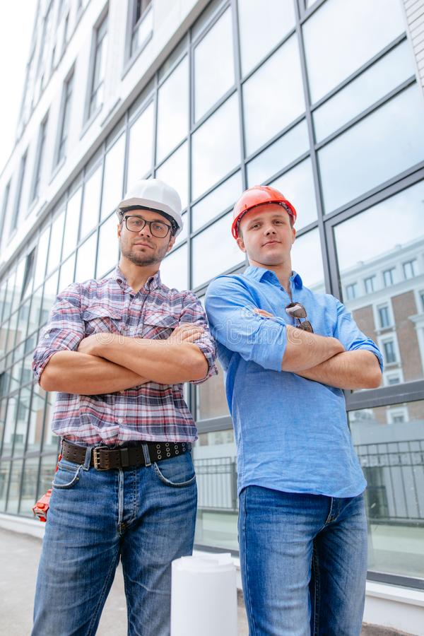 Experienced business people in casual clothes and hardhats posing to the camera royalty free stock image