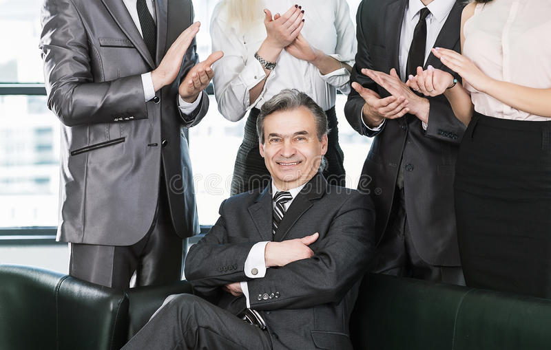 Experienced businessman at the age of applause in the background of their employees royalty free stock image