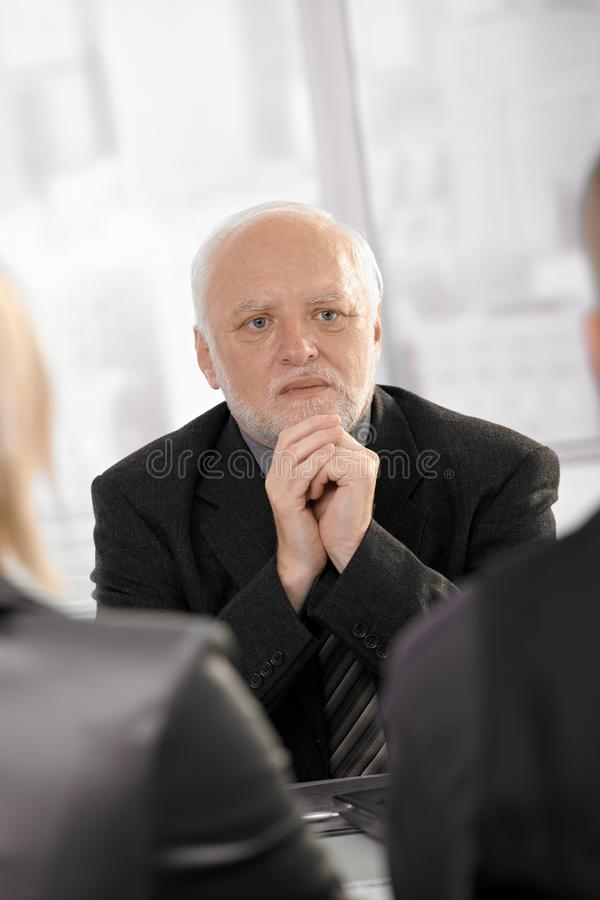 Experienced businessman concentrating. Experienced senior businessman concentrating, looking serious on meeting royalty free stock images