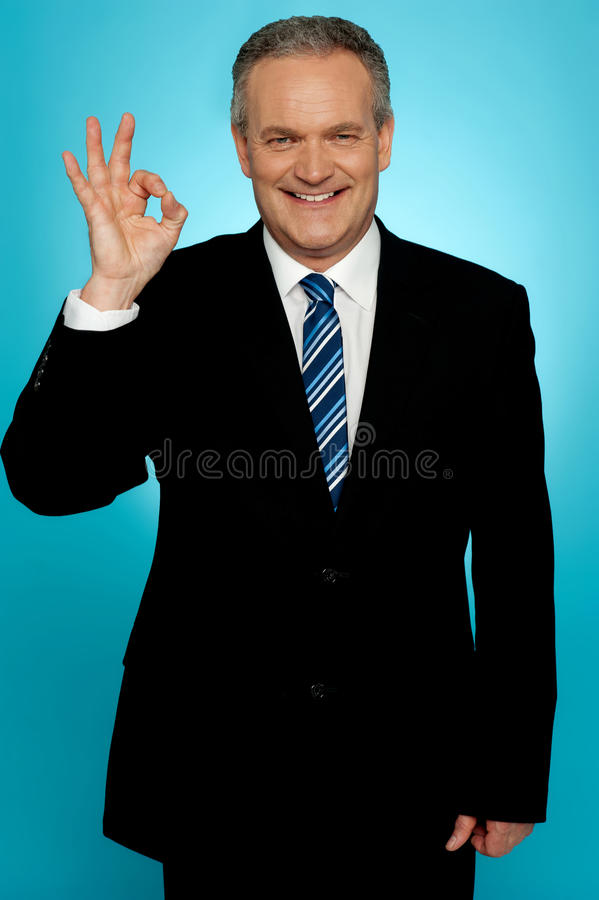 Experienced businessman showing okay sign royalty free stock image