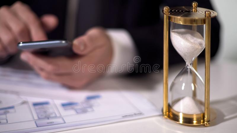 Experienced businessman using mobile app on gadget, sandglass measuring time royalty free stock images