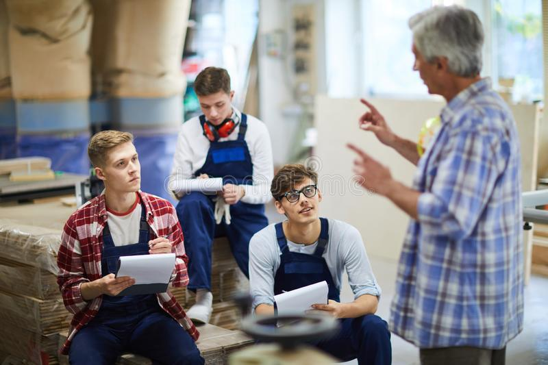 Experienced carpenter holding lecture for interns stock image