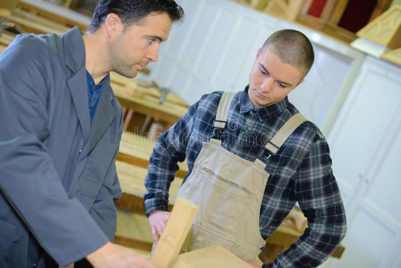 Experienced carpenter teaching teenage boy royalty free stock photography