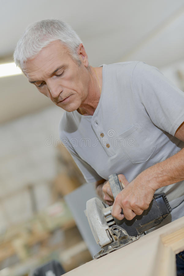 Experienced carpenter using circular saw royalty free stock photography