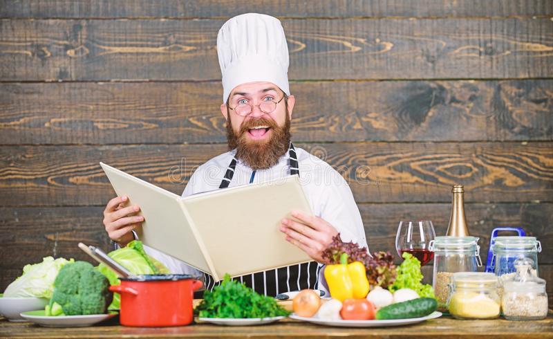 Experienced chef cooking excellent dish. This recipe is just perfect. Man bearded hipster read book recipe near table stock photography