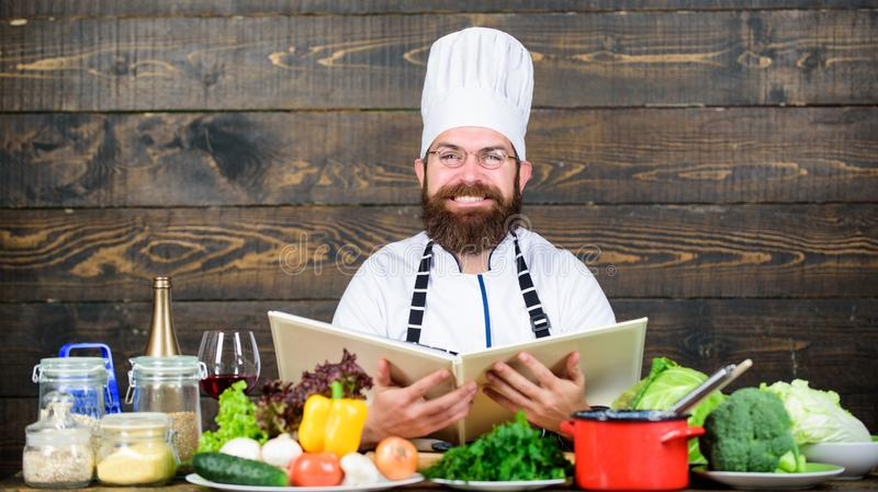 Experienced chef cooking excellent dish. This recipe is just perfect. Vegetarian recipe. Culinary arts. Man bearded. Hipster read book recipe near table fresh stock images