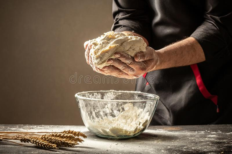 An experienced chef in a professional kitchen prepares the dough with flour to make the bio Italian pasta. the concept of nature, stock photo
