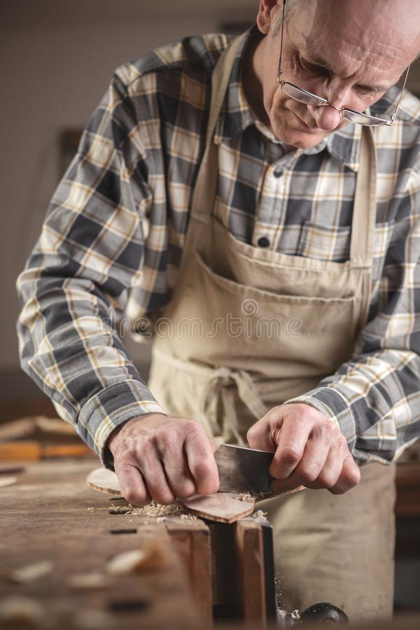 Mature carpenter scraping down a piece of wood. Experienced craftsman working manually on a piece of wood. He is wearing an apron and a checkered shirt and stock photos