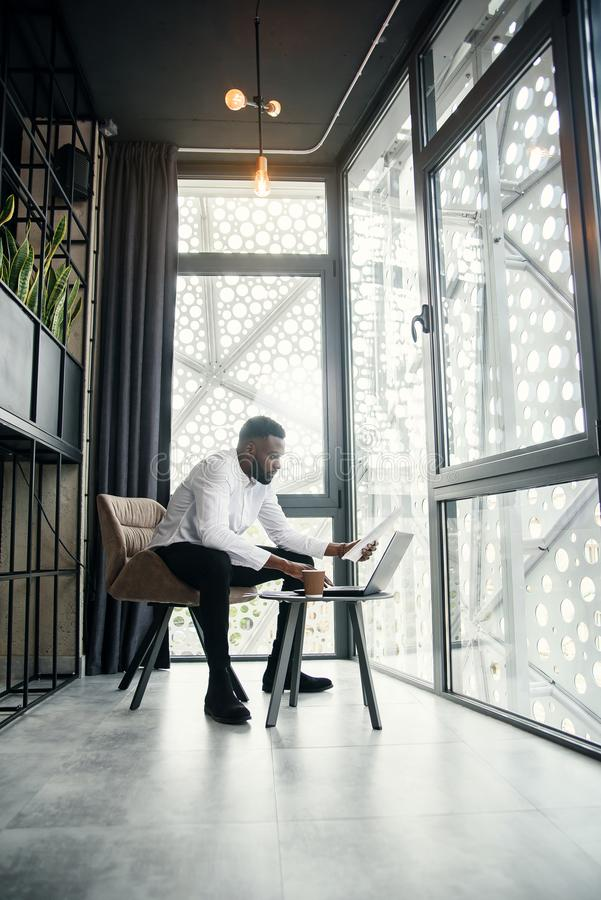 Experienced dark-skinned businessman with well-groomed beard working at the laptop in the specially designated room in royalty free stock images
