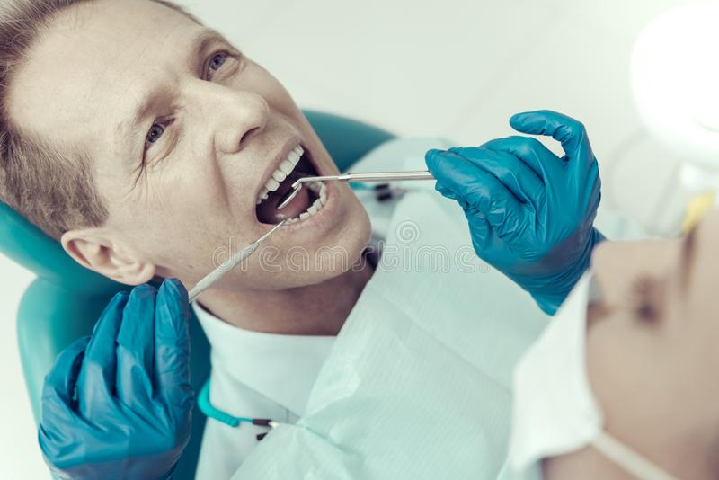Experienced dentist in blue gloves examining the patient royalty free stock image