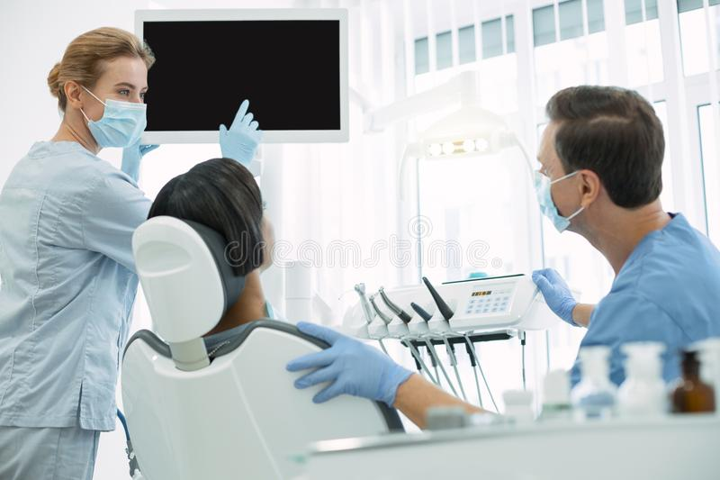 Experienced dentists working with their patient royalty free stock photo