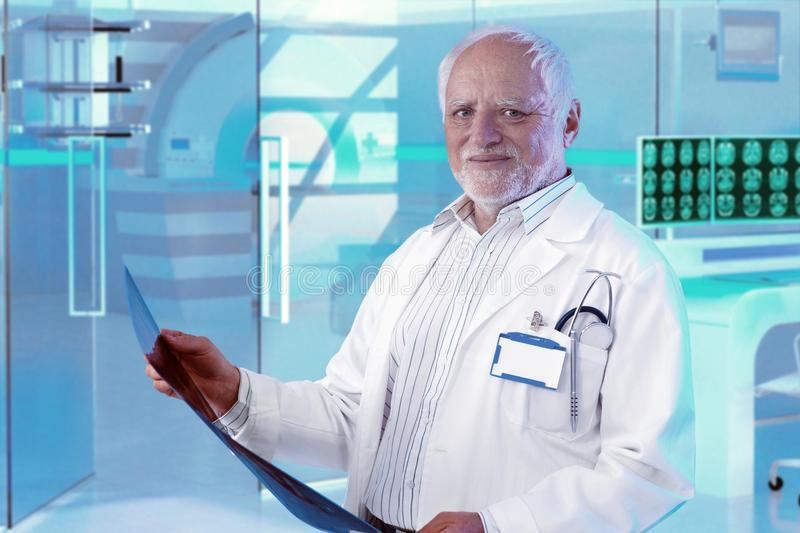 Experienced doctor checking MRI scan at hospital. Experienced white-haired male doctor checking MRI scan at hospital royalty free stock photography