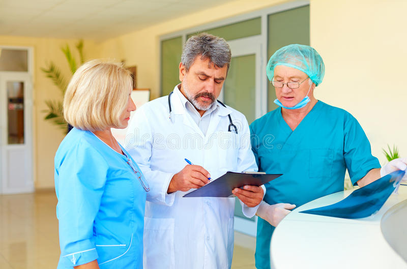 Experienced doctor and medical staff consulting about health record in hospital royalty free stock photo