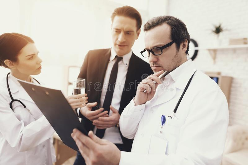 Experienced doctor with nurse and troubled businessman looks at results of medical examination. stock photography