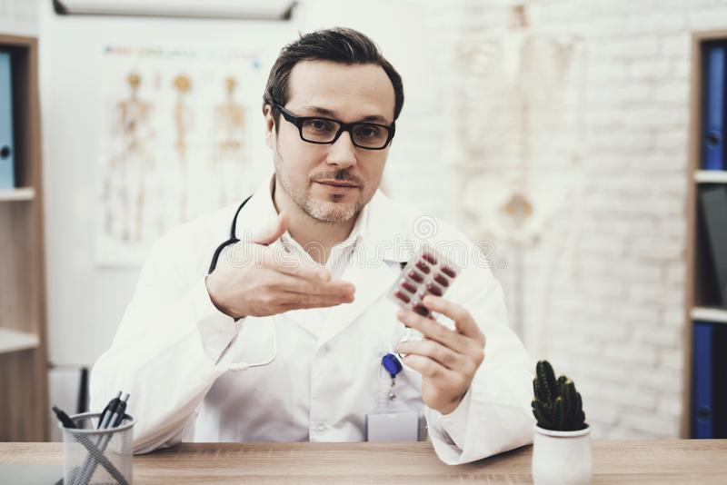 Experienced doctor with stethoscope in medical dressing gown holds blister pack of tablets. stock photo