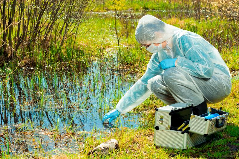 Experienced ecologist on the shore of a forest lake takes water. Samples stock photos