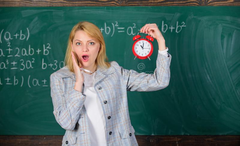 Experienced educator start lesson. She cares about discipline. What time is it. Woman teacher hold alarm clock. Girl. Experienced educator start lesson. She stock image