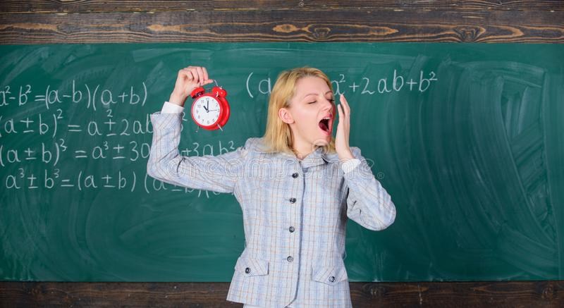Experienced educator start lesson. She cares about discipline. Woman teacher hold alarm clock. Girl formal wear school. Lecturer. What time is it. Lessons royalty free stock images
