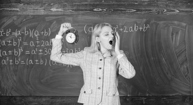 Experienced educator start lesson. She cares about discipline. Woman teacher hold alarm clock. Girl formal wear school stock photo
