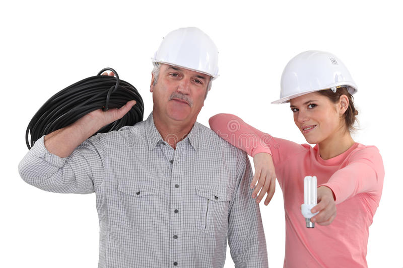Experienced electrician and young apprentice. Cxperienced electrician and young female apprentice royalty free stock image