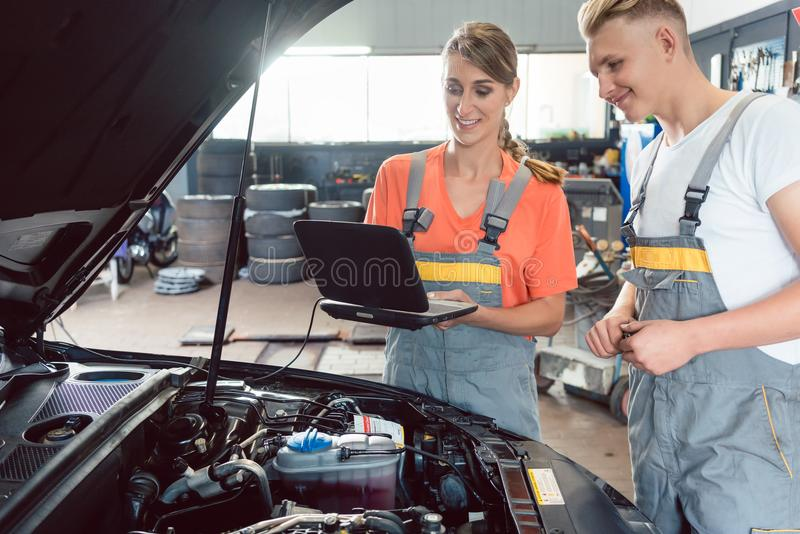 Experienced female auto mechanic checking the engine error codes. Scanned by a car diagnostic software while standing next to a motivated apprentice royalty free stock photos