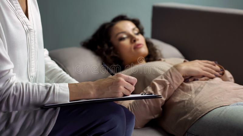 Experienced female psychologist writing advice to sad patient at therapy session. Stock photo royalty free stock photo