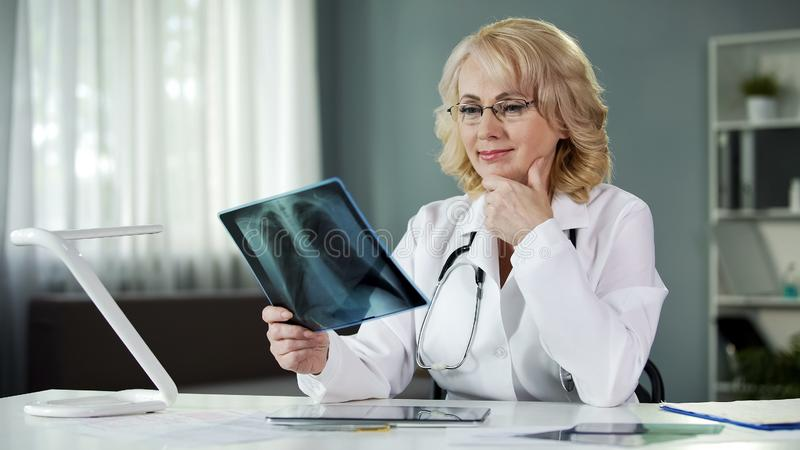 Experienced female radiologist studying X-ray picture, qualified diagnostics. Stock photo stock image