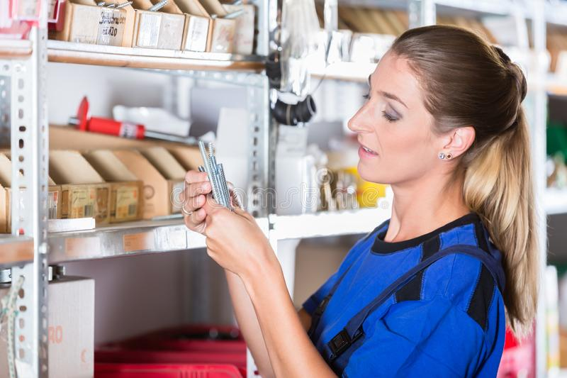 Experienced female worker in a sanitary ware shop with high-quality accessories. Side view of an experienced manual female worker holding various bolts in a royalty free stock photo