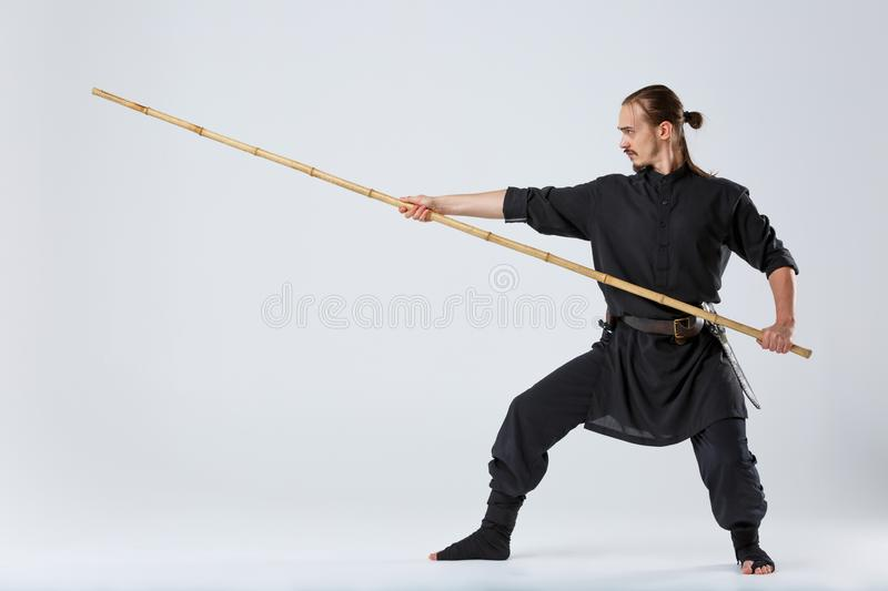 A ninja man, is in a special black kimono, works out the technique of striking with a fighting bamboo stick. royalty free stock photography