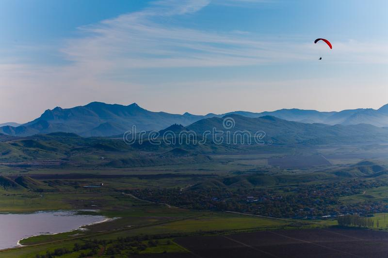 Experienced hang-glider hovering above hilly landscape. Mountain landscape in the Crimea royalty free stock images