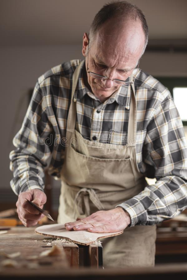 Experienced instrument maker carefully using his hand to check a piece of a mandolin. Experienced instrument maker carefully using a hand to examine a wooden royalty free stock images