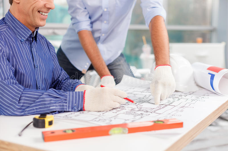 Experienced male architects are working on new. Close up of arms of two successful engineers designing the building. The senior worker is sitting at the table royalty free stock photos
