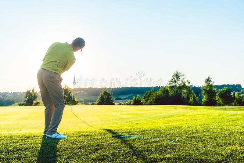 Experienced male golfer hitting the golf ball towards the cup stock image