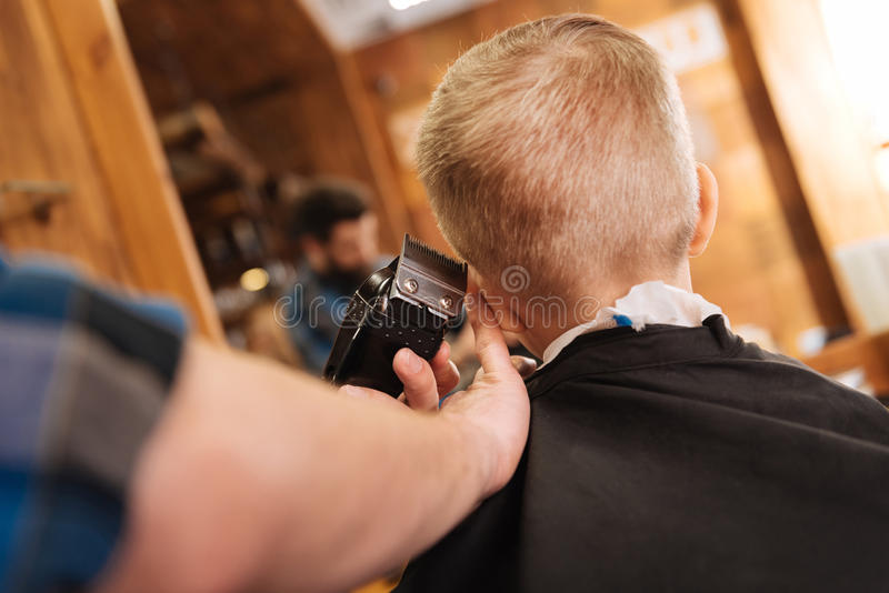 Experienced male hairdresser working with hair cutting machine. Modern hairstyle. Experienced nice male hairdresser holding a hair cutting machine and using it royalty free stock images