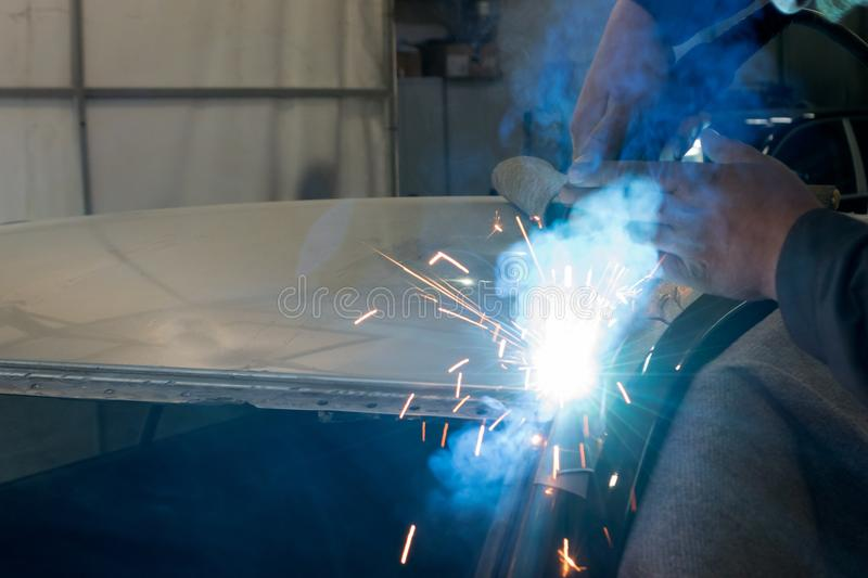 Experienced man performs work on body repair car with a welding machine. royalty free stock photo