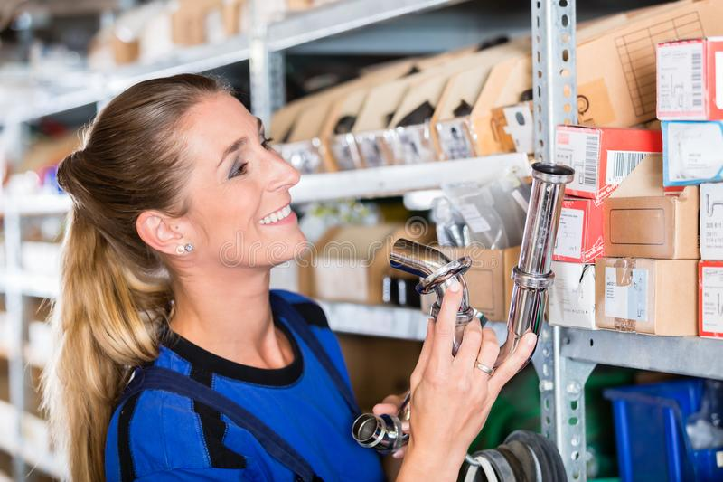 Experienced manual female worker in a sanitary ware shop. Side view of an experienced manual female worker holding various bolts in a modern sanitary ware shop stock image