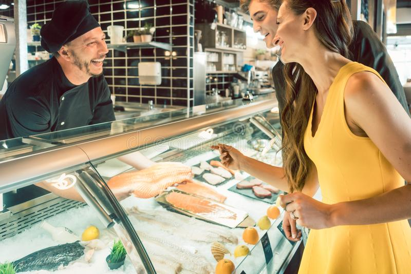 Experienced chef taking a fresh fish from the freezer to cook it. Experienced master chef taking a fresh fish from the freezer to cook it for a female customer stock photos
