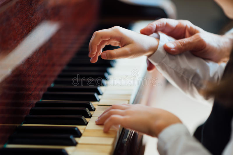 Experienced master piano hand helps the student royalty free stock photos