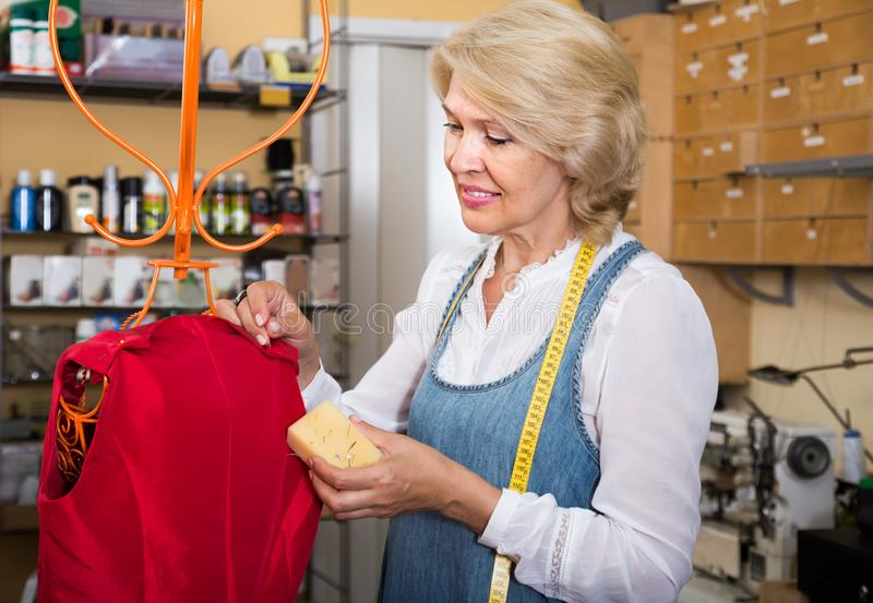 Mature woman sewing gown in clothing workshop. Experienced mature woman sewing gown in clothing workshop royalty free stock image