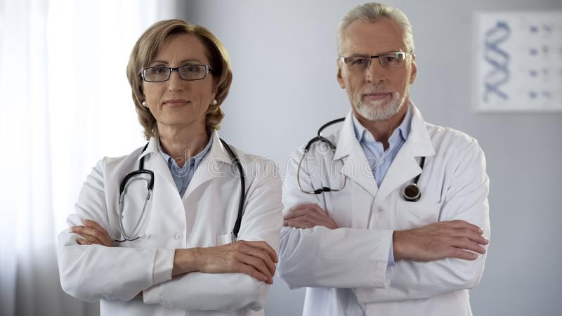 Experienced man and woman doctors looking at camera, arms crossed, guarantee stock images