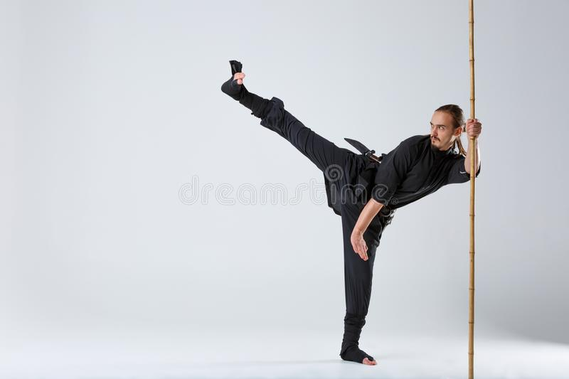 Ninja man, works out the technique of kicking with a battle bamboo stick . stock image