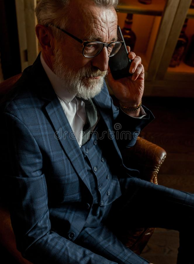 Experienced old private physician talking on smartphone with patient indoors. stock photo