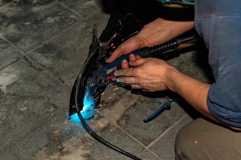An experienced person performs work with a welding machine, fixing metal parts, removing blue smoke and yellow sparks and stock photo