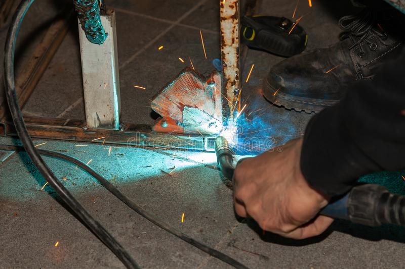 An experienced person performs work with a welding machine, fixing metal parts, removing blue smoke and yellow sparks and stock images