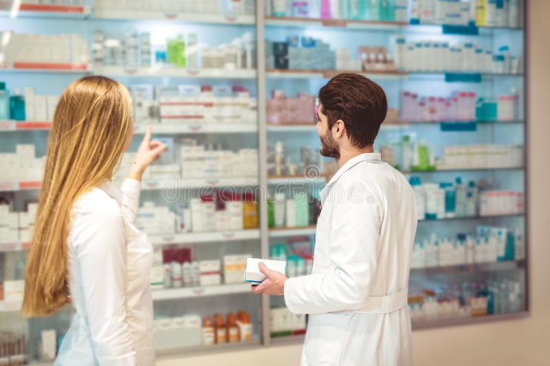 Experienced pharmacist counseling female customer in pharmacy. Experienced pharmacist counseling female customer in modern pharmacy royalty free stock images