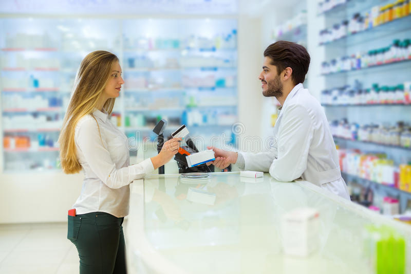 Experienced pharmacist counseling female customer. In modern pharmacy, and women pay with credit card royalty free stock photo